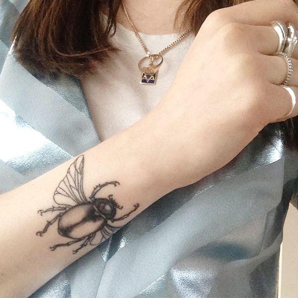 Chica con un bello tatuaje de escarabajo egipcio en su antebrazo