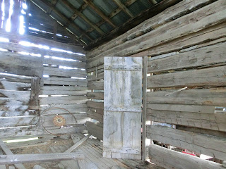 wooden logs with space of chinking, old door, sunlight coming through spaces