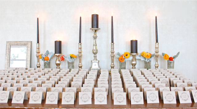 Escort card table design featuring mercury glass votive holders and pillar holders, orange ranunculus and dusty miller