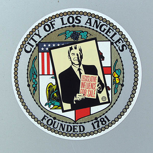 Occupy Los Angeles - sticker on city seal: Ronald Reagan holds sign: Legistlative Influence For Sale
