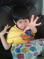 Boy showing five fingers to his father
