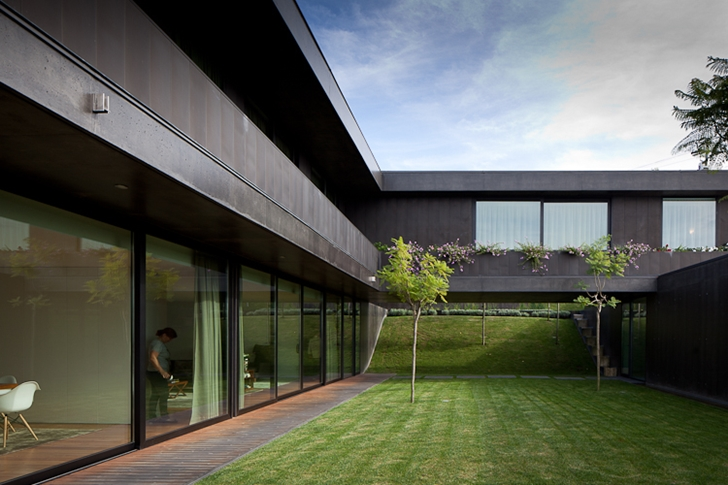 Grass in the backyard of Black Concrete House by Pitagoras Arquitectos