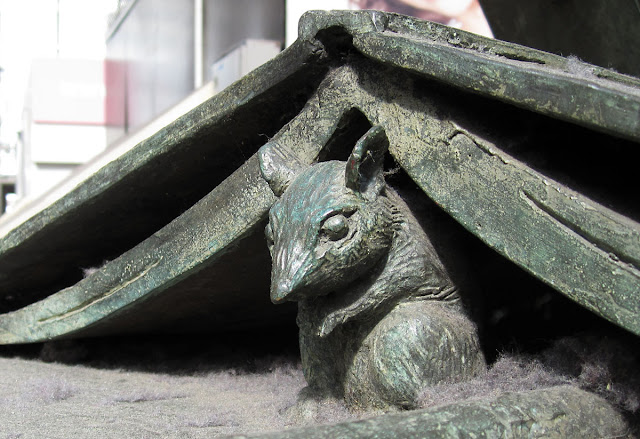 A mouse under a book at the back of the statue of Terence Tenison Cuneo by Philip Jackson in Waterloo Station, London. 19 April 2011.