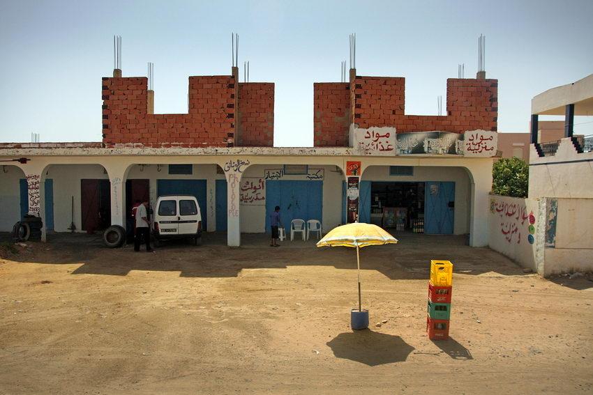 Foto a uma rua em terra com estabelecimentos comerciais e um guarda-sol na frente a dar sombra a grades de bebidas