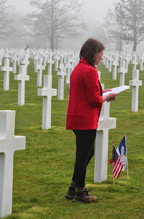 Student reading at the grave of an American soldier in Normandy, France at the Omaha Beach American cemetery