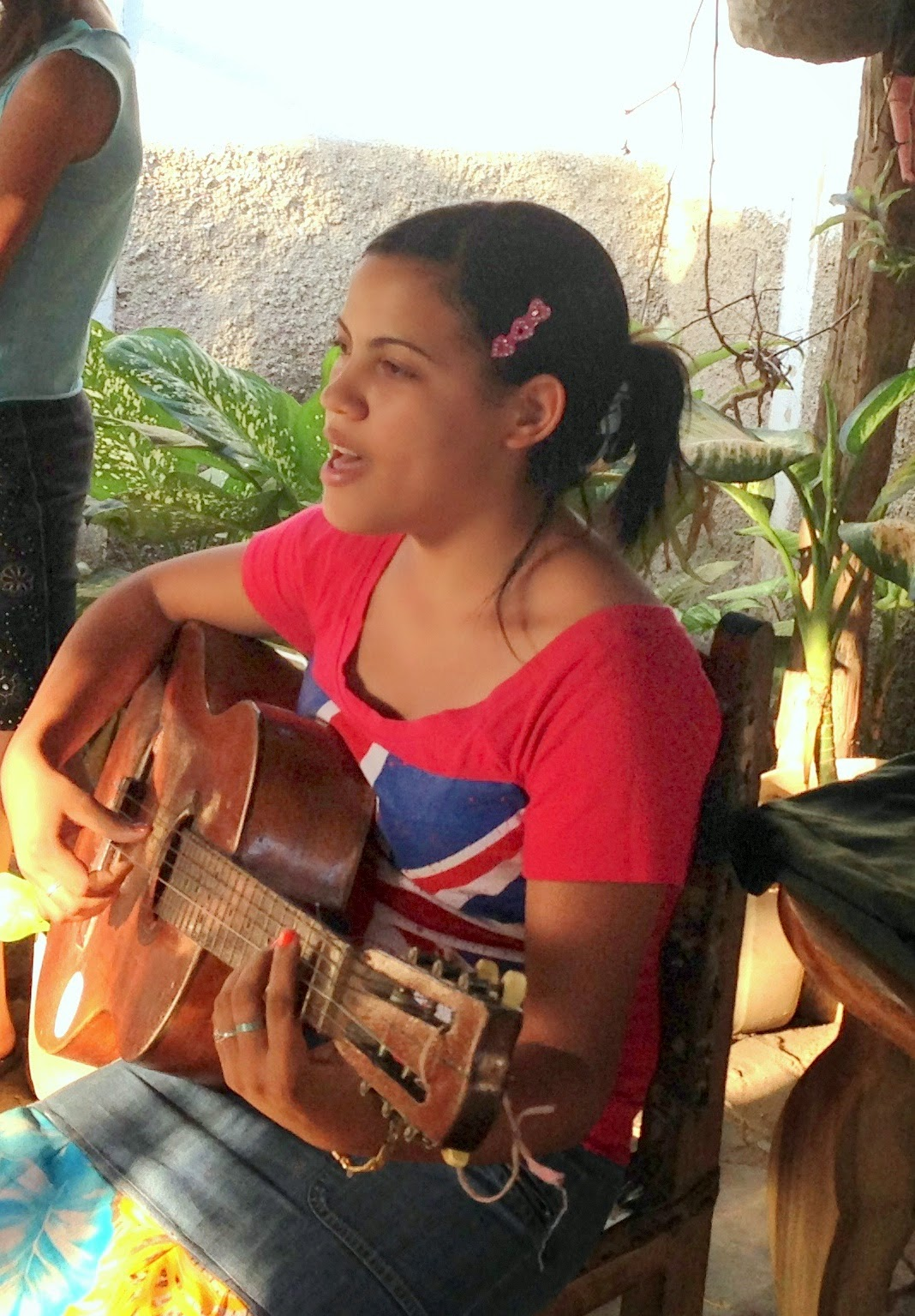 girl in red shirt with guitar singing