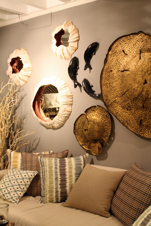 Blick auf ein Sofa mit Kissen und Fischen aus Stein an der Wand