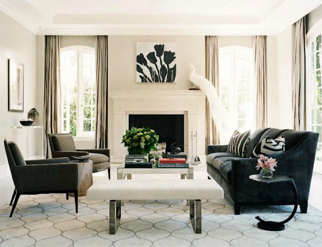 Living room with a gray, black and white color scheme, a white molded fireplace with a white peacock on the mantel, large windows, a creasent moon side table, a valance covering the top of the floor length curtains, and a gray sofa facing two matching arm chairs.