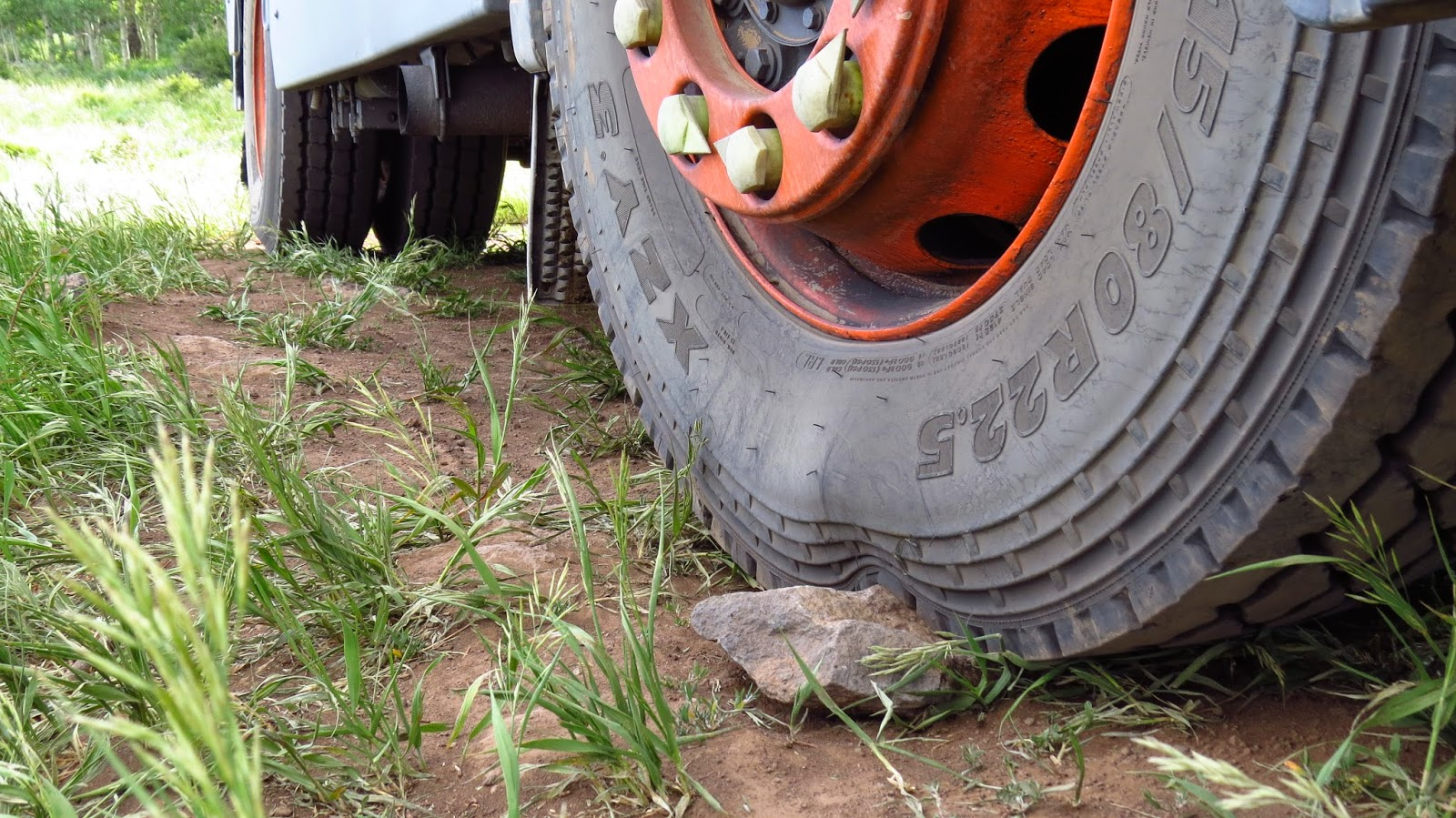 315/80R22.5 Michelin XZY3 tire deforms over a small rock on Jim the overland expedition motorhome