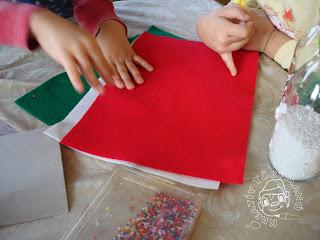 Szöveg: Ezek itt a hozzávalók. Kép: Drapp asztalterítővel letakart asztalon piros, fehér és zöld nemezlapok, két a képbe belogó izgő-mozgó gyerekkéz, lapos átlátszó dobozban színes gyöngyök.