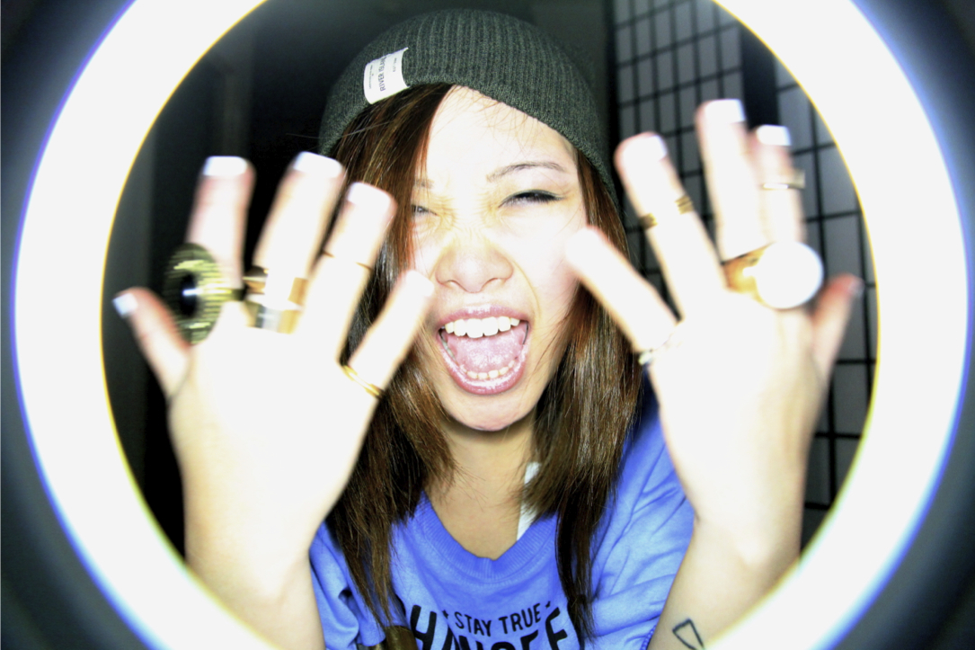 Girl moving hands with rings in the air, wearing Sin Star Sweater