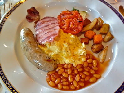 english breakfast with potato, beans, sausage, eggs and ham