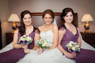 Bride with softly pinned up hair with her bridesmaids wearing their hair swept to the side incorporating a braid
