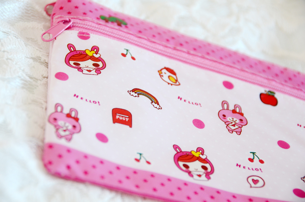 The pouch features a polka-dot and stars pattern in light pink with cute chibi cartoon characters.