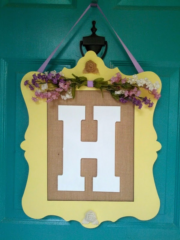 "monogram ""H"" sign hanging on teal door"