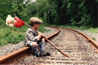 Kid on railroad tracks running away from home with hobo pack