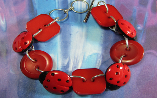 Cute bracelet has ladybugs and bold red buttons linked together with silver loops