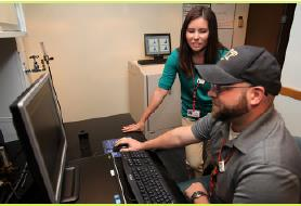 Claudia and Dustin Van Dame, senior nuclear specialist,  review dosimeter processing information.