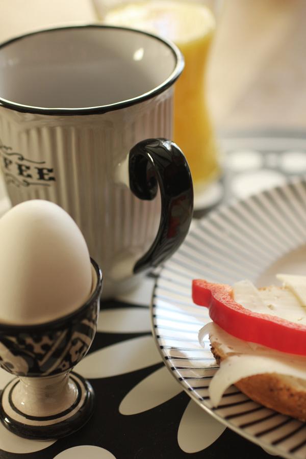 frukost. svart och vit äggkopp från allrum. kaffekopp. glas med juice. tallrik zebra. svart och vitt bordsunderlägg.