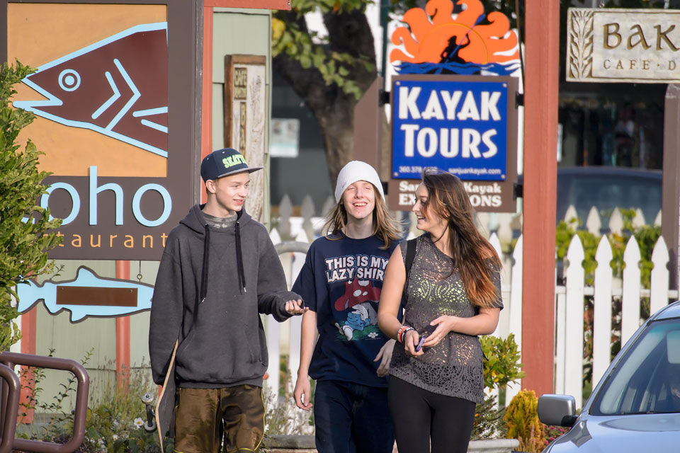 Teens on Nichols Street, with Coho Restaurant, San Juan Kayak Expeditions, and Cafe Demeter in the background.