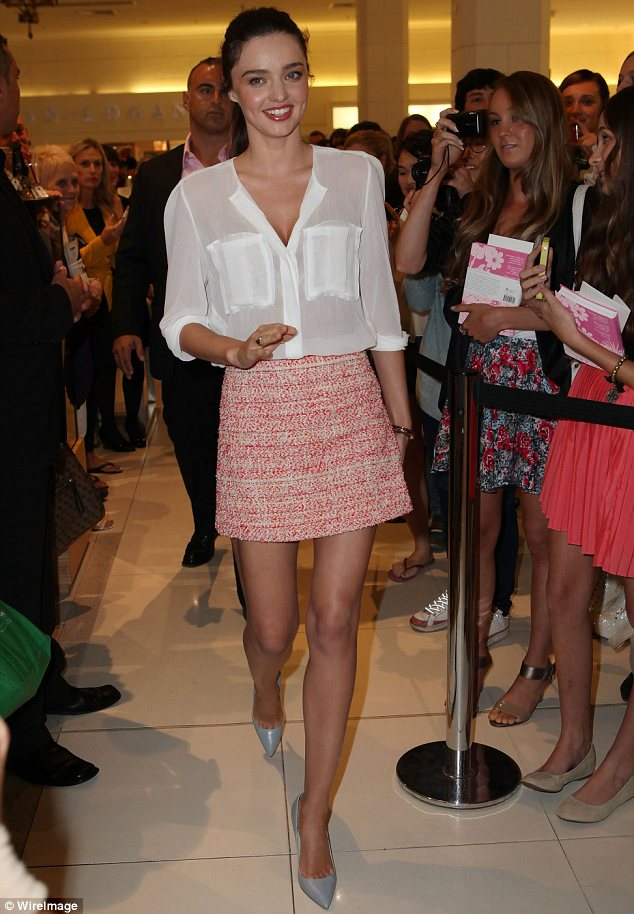 Miranda Kerr promotes her skincare line in a sheer blouse and miniskirt