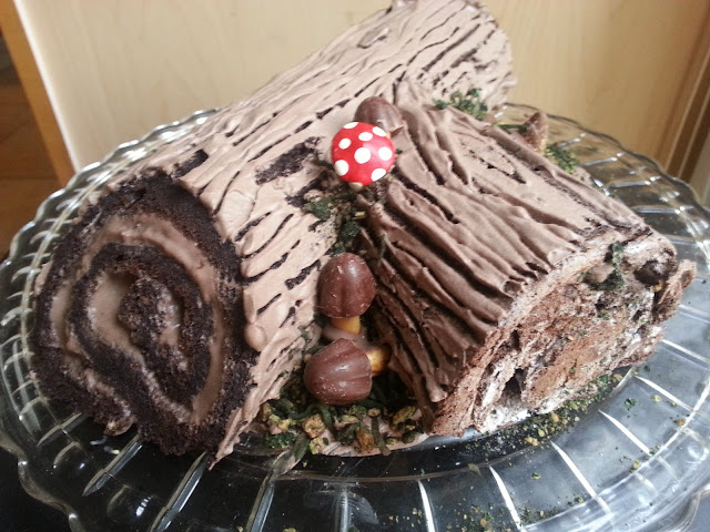 Log cake (Buche de Noel) with bark frosting, candy mushrooms, and edible moss