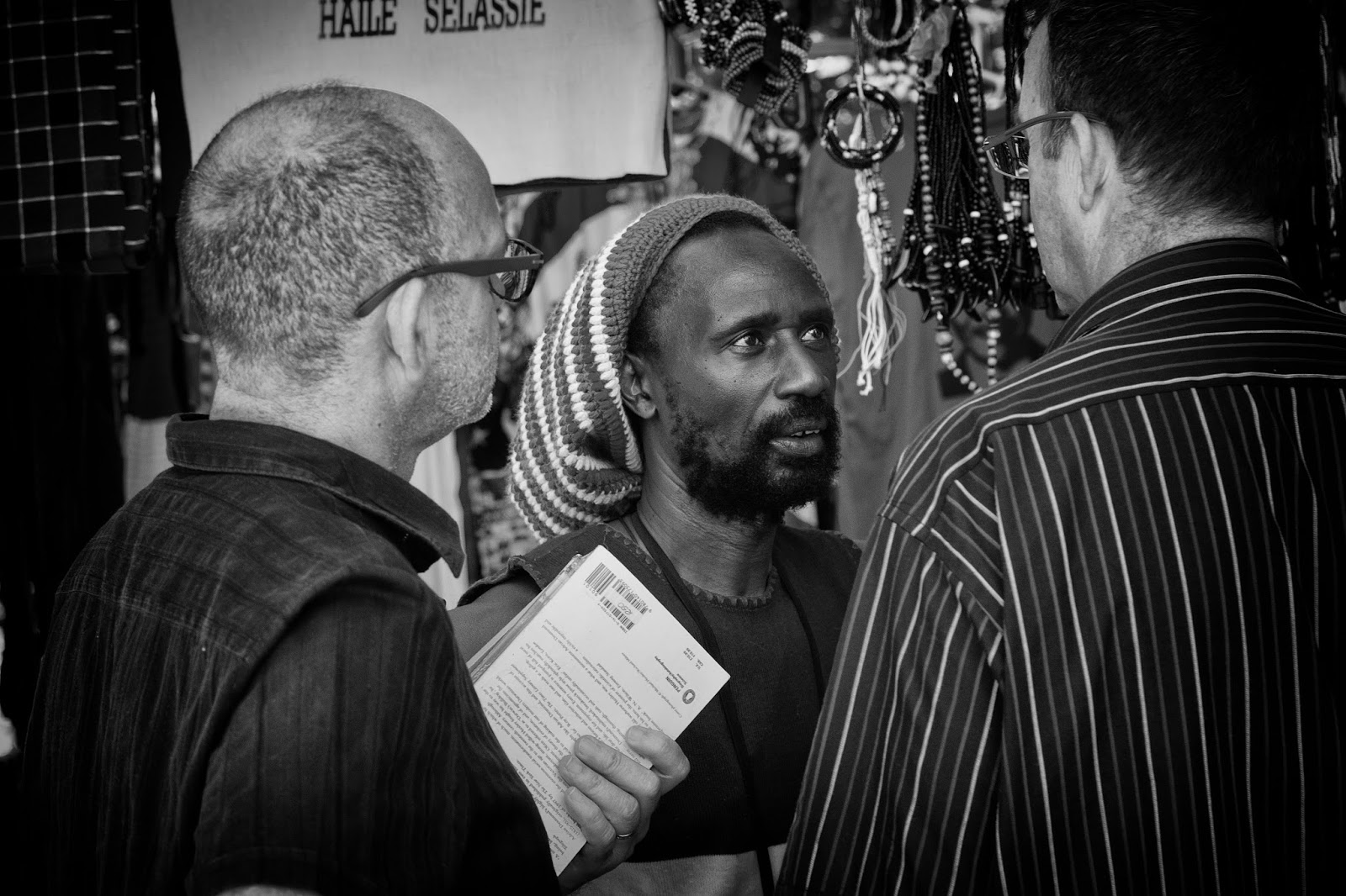 A rasta talks to two men in spectacles