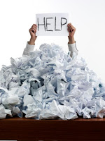 "pile of scrunched up paper on a desk and a sign saying ""help"""