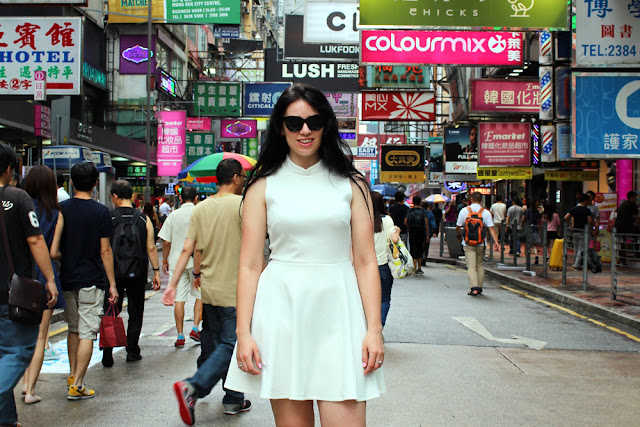 Fashion blogger Emma Louise Layla in white Dorothy Perkins dress on a busy Hong Kong street