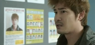 Kang Ji Hwan 강지환 as Kim Ji Hyuk, stands next to his wanted poster in the police station.
