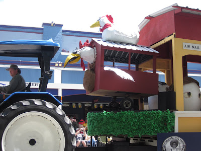 A tractor pulling a float with a flying chicken