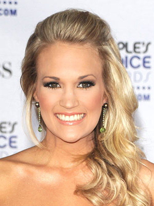 Carrie Underwood's wavy, side-swept hairstyle has a neatly pinned back section on top.