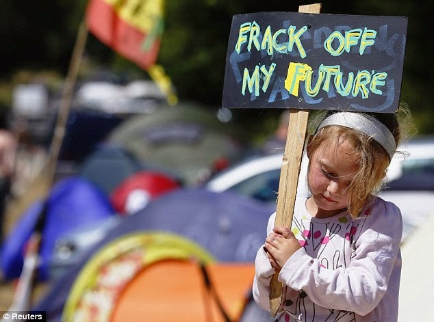 A young protestor holds a placard at the entrance gate belonging to a site run by Cuadrilla Resources (Credit: www.dailymail.co.uk)(Credit: ) Click to enlarge.