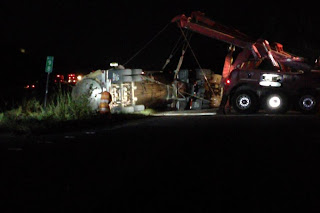 Photo of tanker rollover with large tow truck on scene to upright it.