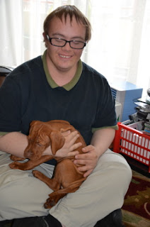 young man with Down syndrome holds vizsla puppy