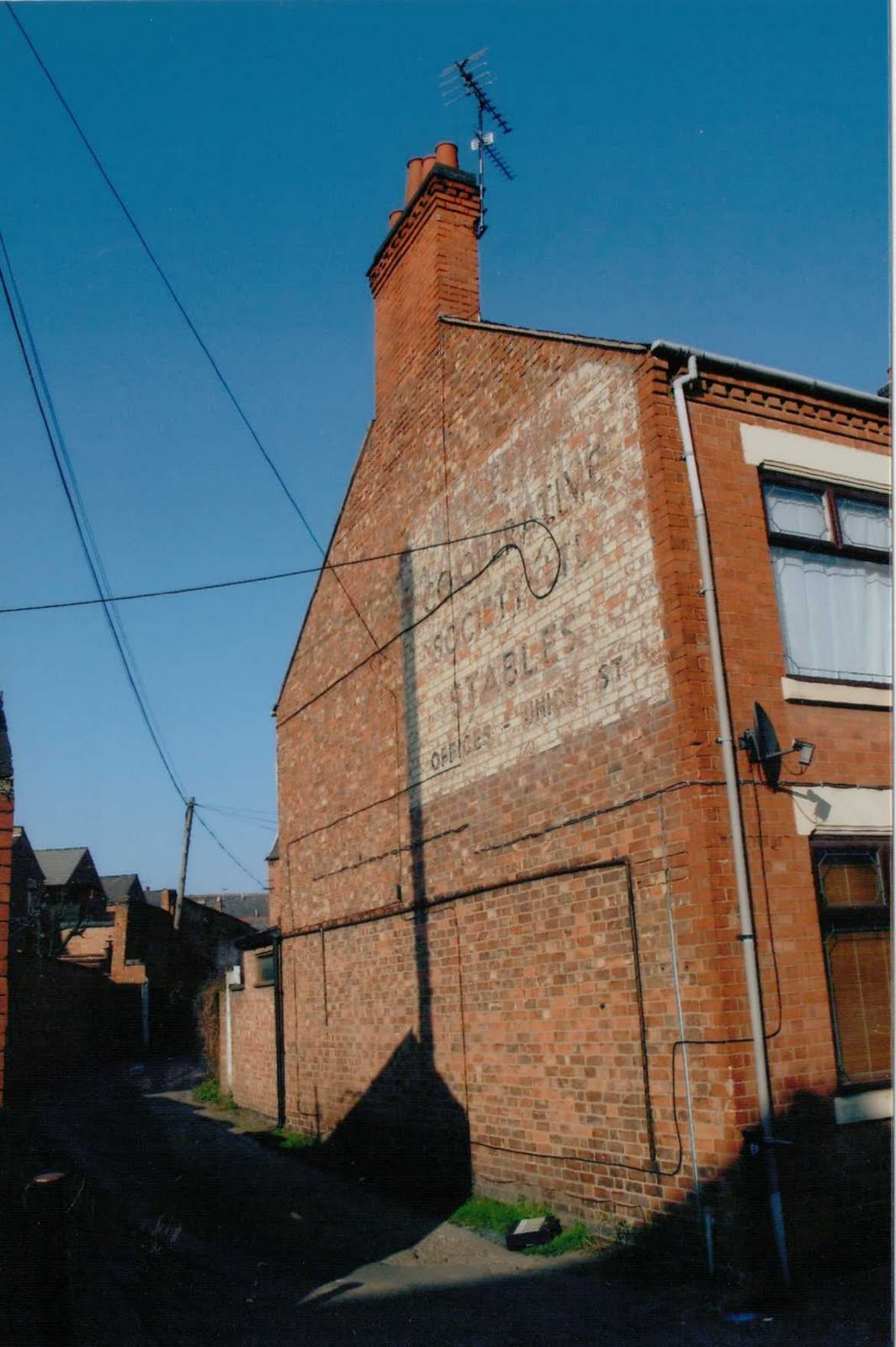 (The other entry to the stables on Battenberg Road as it is now. The space houses several small businesses. There aren't many of those wall-painted signs ...
