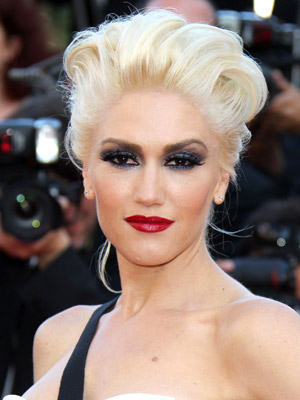 Gwen Stefani goes glam with a teased updo and dramatic makeup.