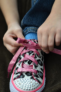 learning to tie shoes, wrap the lace around the loop