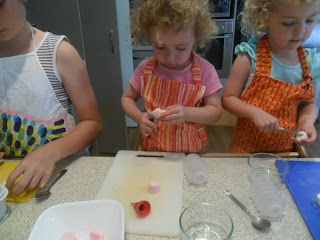 Snipping marshmallows with scissors to decorate biscuits.