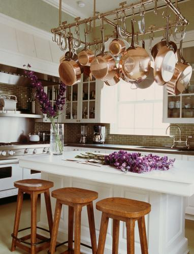 White Kitchen With Stove And Island Pot Racks Above