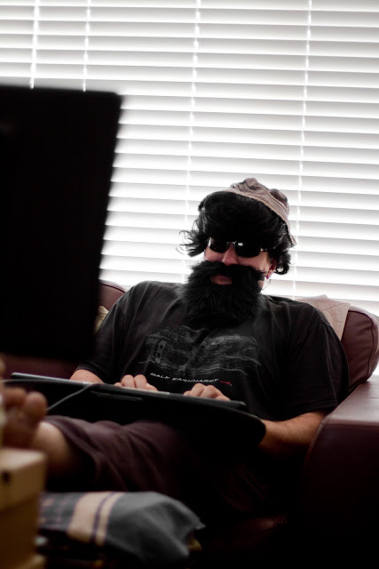 fake beard sitting at computer