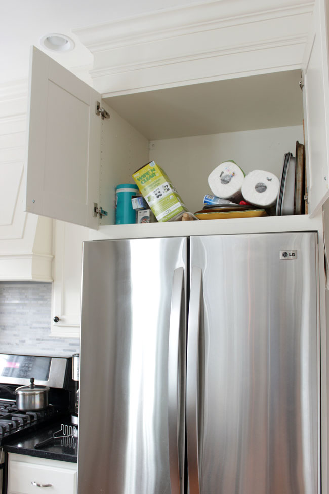 Trend cabinet above the stainless steel fridge disorganized