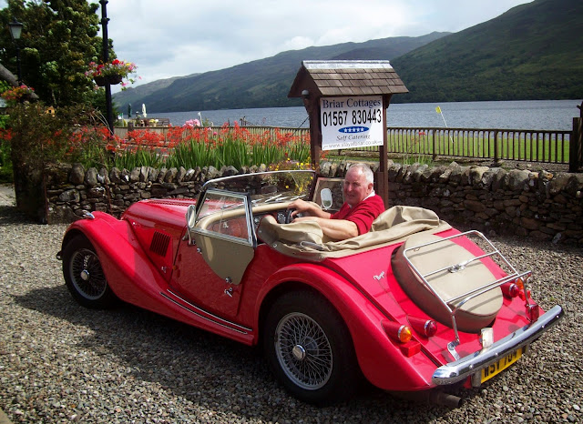 Fraser poses in guests classic Morgan at Briar Cottages, Lochearnhead