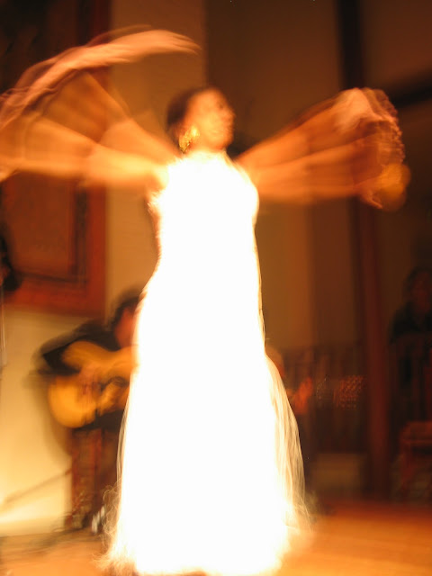 A flamenco dancer in madrid spain wearing a white dress and dancing