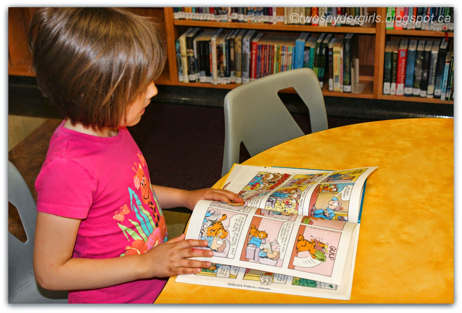 Child reading a book at the library