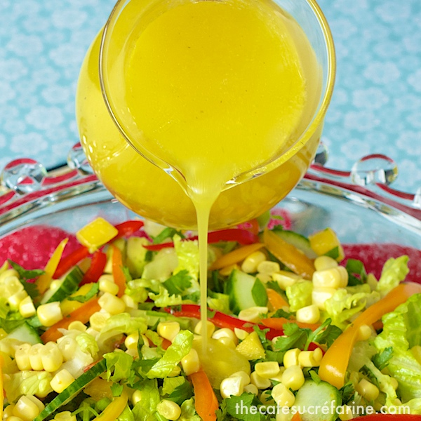 Photo of Sunny Honey Vinaigrette being poured over a platter of Farmer's Market Salad.