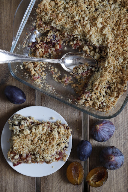 A crumble dish and plated slice on a dark wooden background