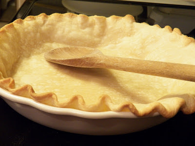 Patting down air bubbles on a partially baked pie crust