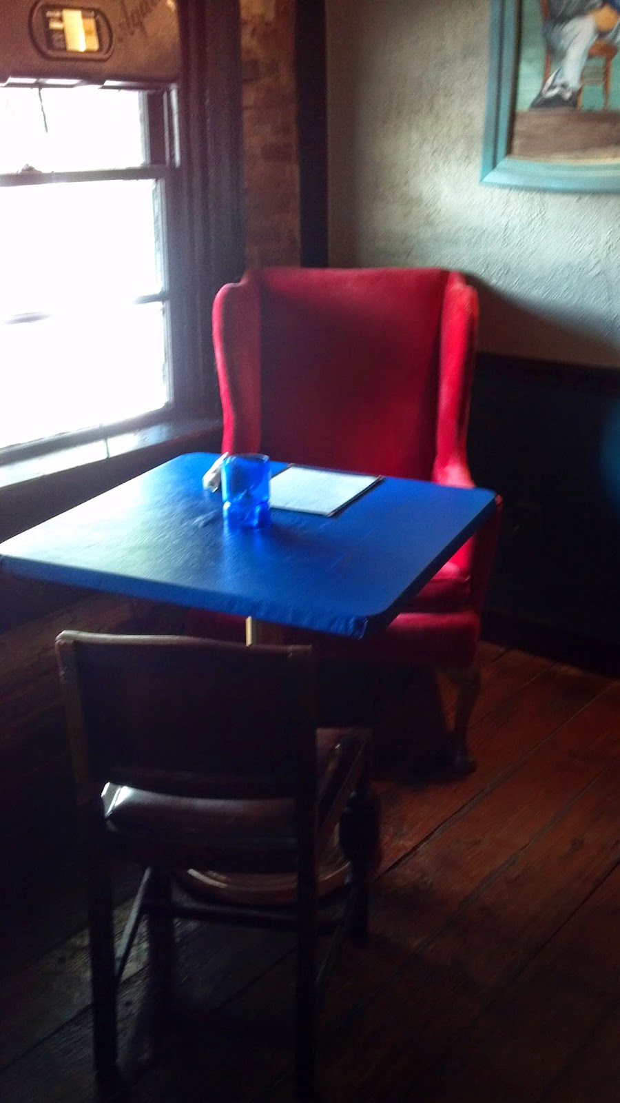 Red chair by window in One Blue Duck