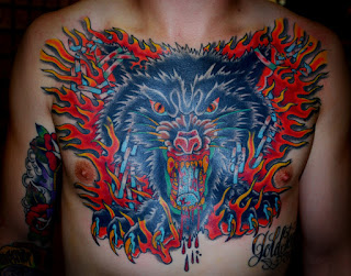 Chest piece tattoo of a large angry wolf head engulfed in flames by tattoo artist Jason Kunz for Triumph Tattoo